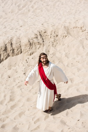 high angle view of Jesus in robe, red sash and crown of thorns walking on sand in desert Stock Photo