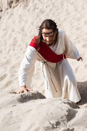 high angle view of Jesus in robe, red sash and crown of thorns climbing sandy hill in desert