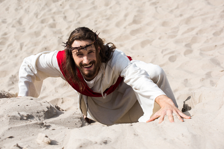 high angle view of smiling Jesus climbing sandy hill in desert and looking at camera