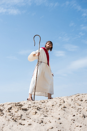 Jesus in robe, red sash and crown of thorns walking on sandy hill with staff in desert Stock Photo