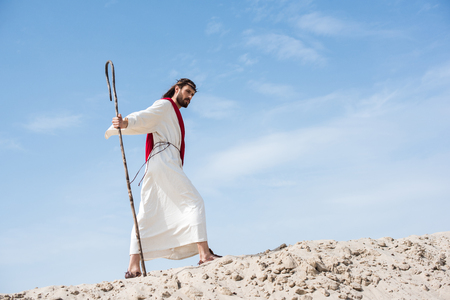 side view of Jesus in robe, red sash and crown of thorns walking on sandy hill with wooden staff in desert