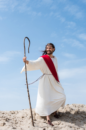 smiling Jesus in robe, red sash and crown of thorns standing with wooden staff in desert Stock Photo