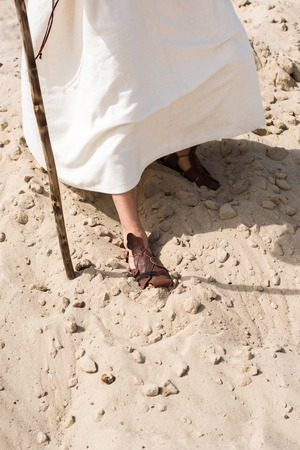 cropped image of Jesus in robe and sandals walking in desert with wooden staff 版權商用圖片