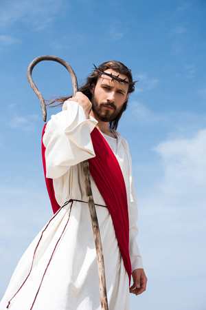 low angle view of Jesus in robe, red sash and crown of thorns standing with wooden staff in desert and looking at camera