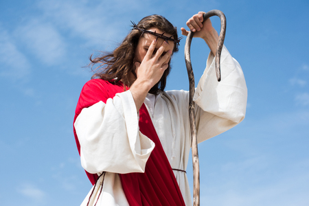 low angle view of Jesus in robe, red sash and crown of thorns standing with wooden staff in desert and touching forehead Stock Photo
