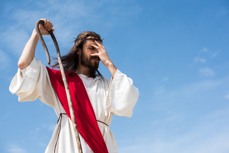 Jesus in robe, red sash and crown of thorns standing with wooden staff in desert and touching forehead