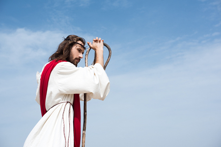 side view of Jesus in robe, red sash and crown of thorns leaning on wooden staff against blue sky