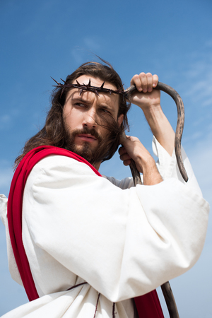 portrait of Jesus in robe, red sash and crown of thorns leaning on wooden staff against blue sky
