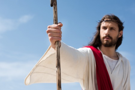 selective focus of Jesus in robe, red sash and crown of thorns holding wooden staff in desert