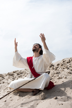 smiling Jesus in robe, red sash and crown of thorns sitting in lotus position with raised hands and talking with god on sand in desert