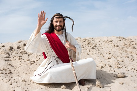 Jesus in robe, red sash and crown of thorns sitting in lotus position on sand in desert and waving hand Stock Photo