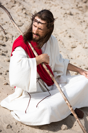 Jesus in robe, red sash and crown of thorns sitting in lotus position on sand in desert and looking away Stock Photo