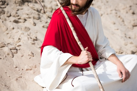 cropped image of Jesus in robe, red sash and crown of thorns sitting in lotus position on sand in desert