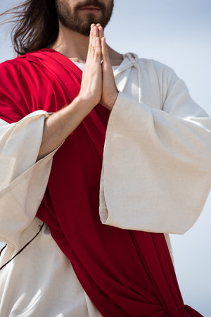 cropped image of Jesus in robe and red sash praying outdoors Stock Photo