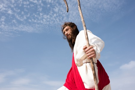 low angle view of Jesus in robe, red sash and crown of thorns standing with staff against cloudy sky