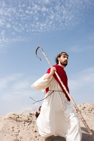 Jesus in robe, red sash and crown of thorns running in desert with staff