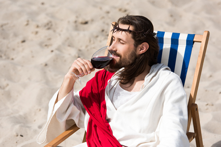 Jesus in robe and red sash resting on sun lounger and drinking red wine in desert Standard-Bild