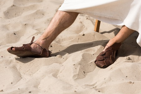 cropped image of Jesus in robe and sandals sitting on sun lounger in desert Stock Photo