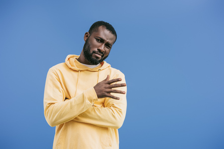 skeptical young african american man gesturing by hand isolated on blue background