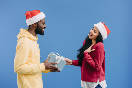 smiling african american man in christmas hat giving gift box to girlfriend isolated on blue background