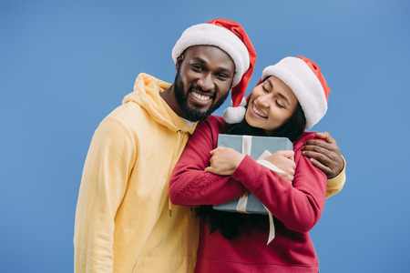 happy african american man in christmas hat embracing girlfriend with gift box isolated on blue background