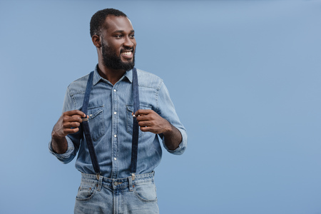 stylish young african american man touching suspenders isolated on blue background