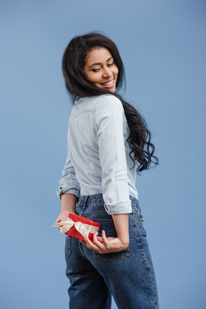 smiling attractive african american girl holding red gift box isolated on blue Foto de archivo