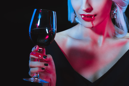 cropped view of vampire woman holding wineglass with blood isolated on black