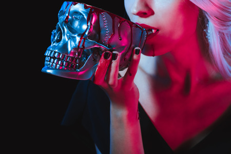 cropped view of vampire drinking blood from metal skull isolated on black