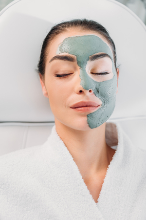 overhead view of beautiful woman with eyes closed and clay mask on face in white bathrobe relaxing in spa salon