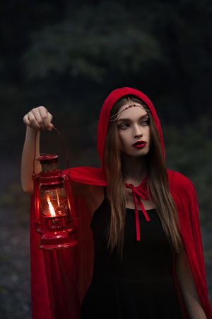 attractive mystic girl in red cloak with kerosene lamp walking in dark forest