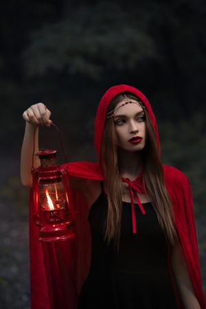 jolie fille mystique en manteau rouge avec lampe à pétrole marchant dans la forêt sombre