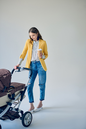 fashionable young woman holding disposable coffee cup and looking at baby stroller on grey Banco de Imagens