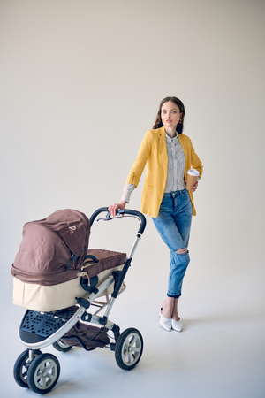 stylish young woman holding disposable coffee cup while standing with baby stroller and looking at camera on grey