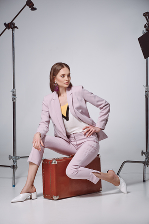 fashionable woman in pink suit sitting on suitcase and looking away in recording studio Banco de Imagens