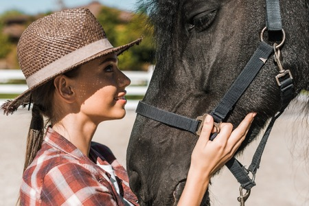portrait of attractive female equestrian touching and looking at horse at ranch