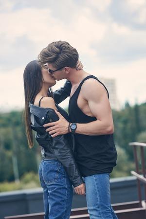 Hermosa pareja interracial caliente besándose en el techo Foto de archivo
