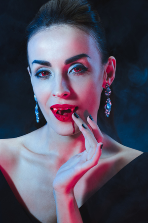 sexy vampire woman licking her fingers on dark background with smoke Stock Photo