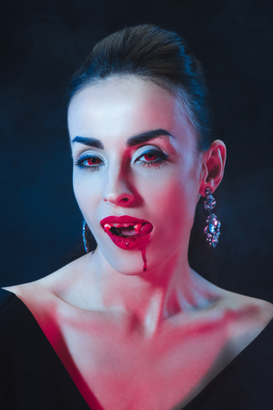 sexy vampire woman licking her lips on dark background