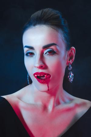 vampire woman licking her lips on dark background