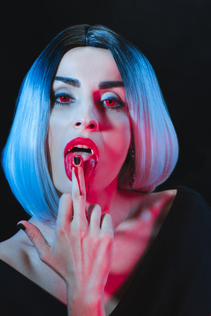 sexy vampire licking her middle finger isolated on black