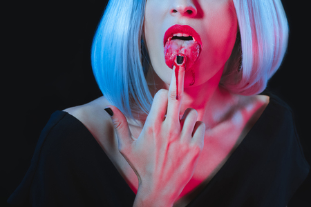 cropped view of vampire woman licking her middle finger isolated on black
