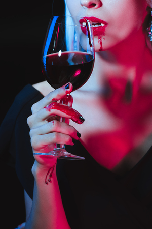 cropped view of vampire drinking blood from wineglass isolated on black