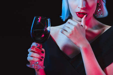 sexy vampire woman holding wineglass with blood and touching her lips isolated on black Stock Photo