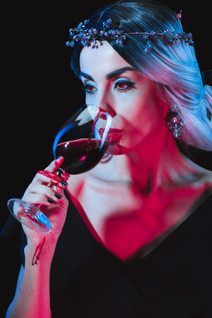 beautiful vampire drinking blood from wineglass isolated on black