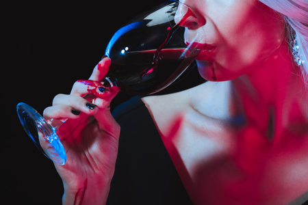 cropped view of vampire woman drinking blood from wineglass isolated on black 스톡 콘텐츠