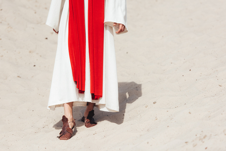 cropped image of Jesus in robe, red sash and sandals walking on sand in desert Stock Photo