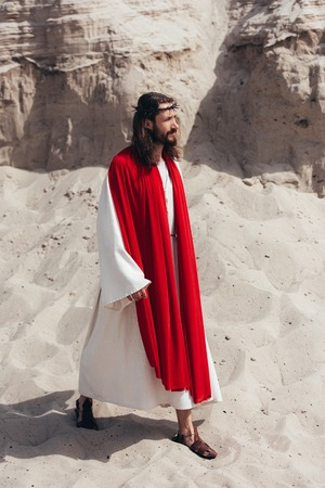 side view of Jesus in robe, red sash and crown of thorns walking in desert