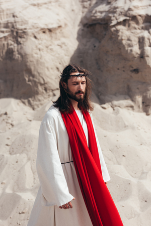 handsome Jesus in robe, red sash and crown of thorns walking with closed eyes in desert Stock Photo