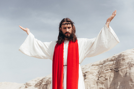 low angle view of Jesus in robe, red sash and crown of thorns standing with raised hands in desert Stock Photo